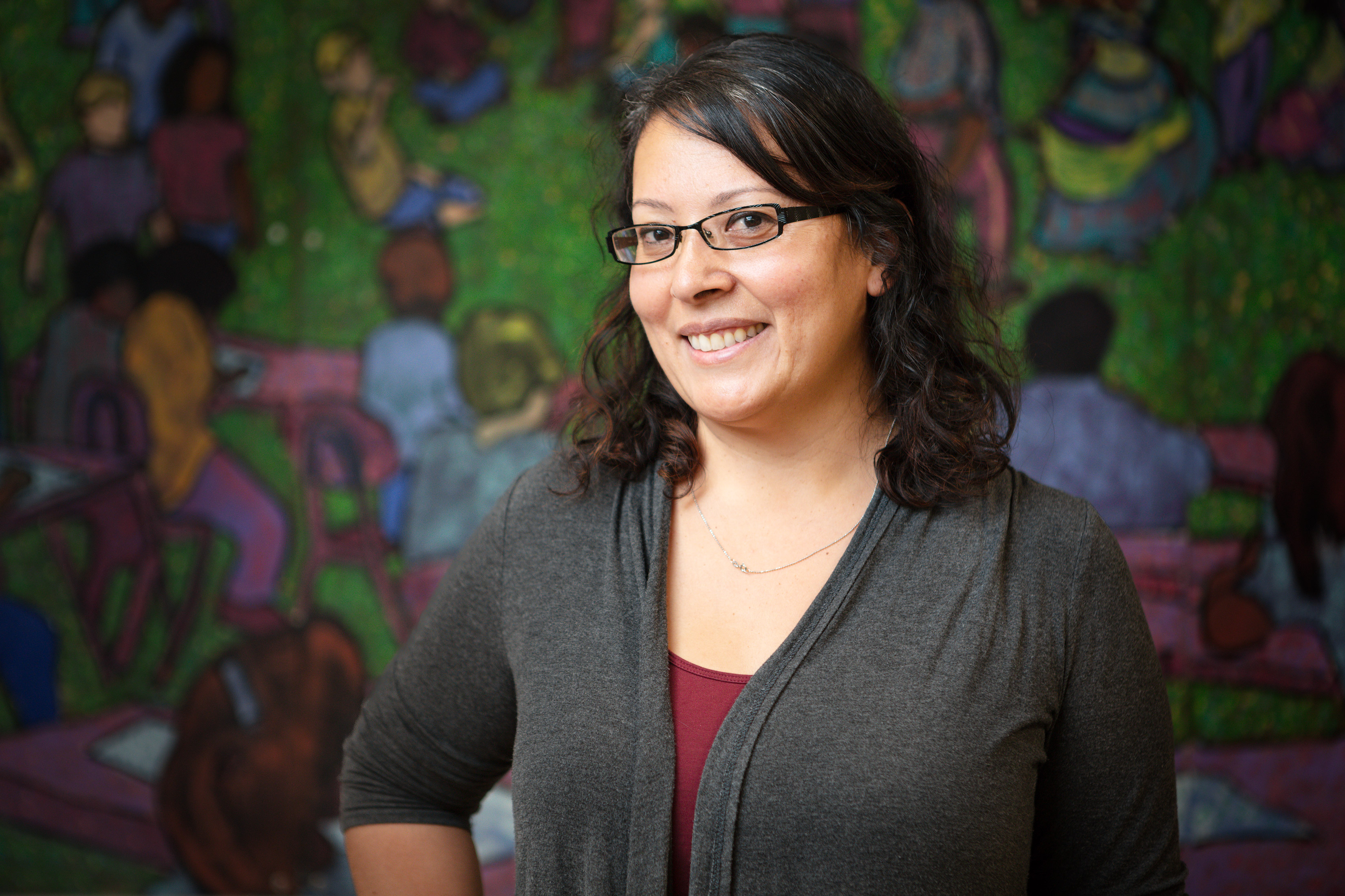 A Denver teacher poses for a portrait in front of a mural at a Denver public school