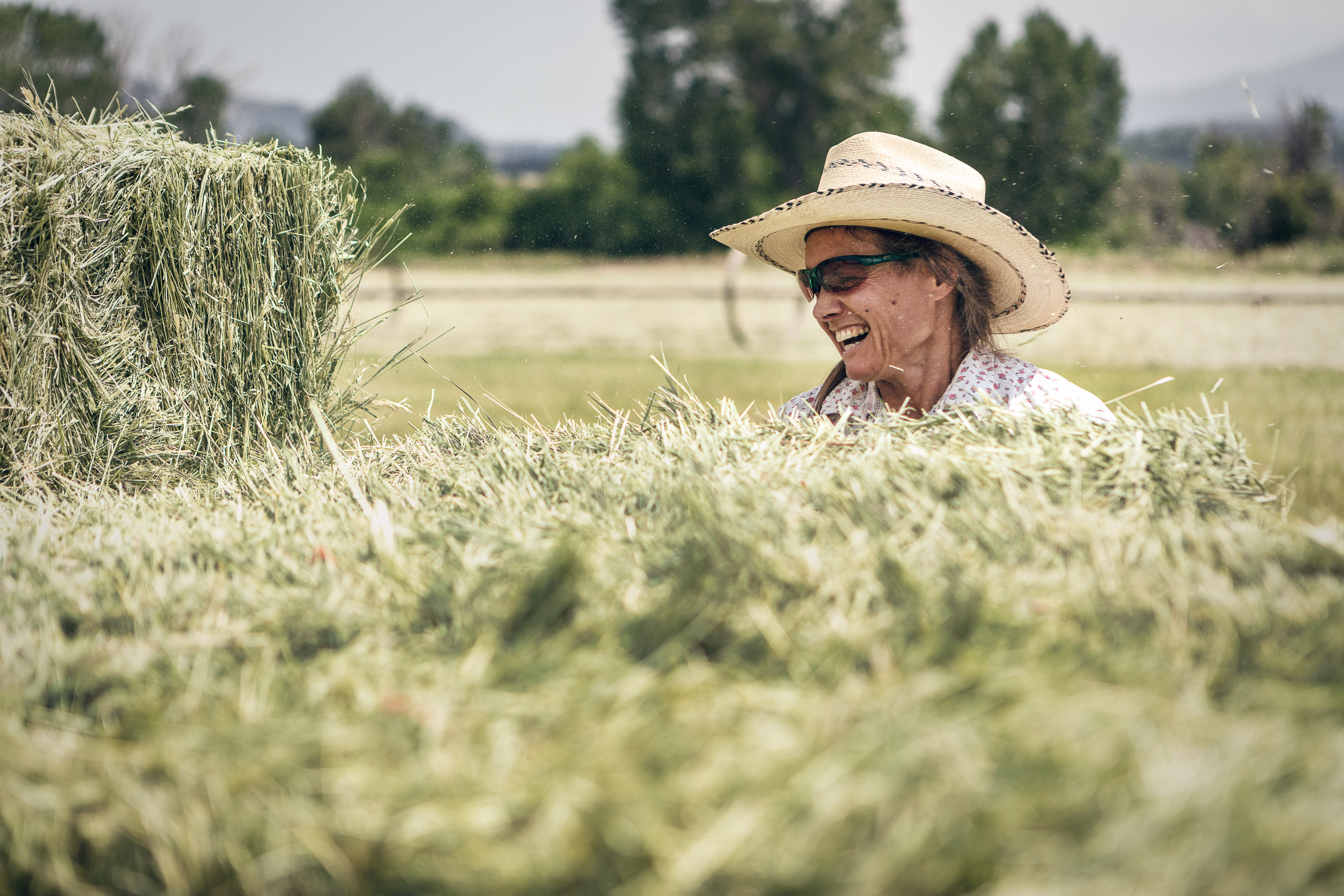 a woman smiles while stacking hay on a trailer on a hay farm in Howard, Colorado