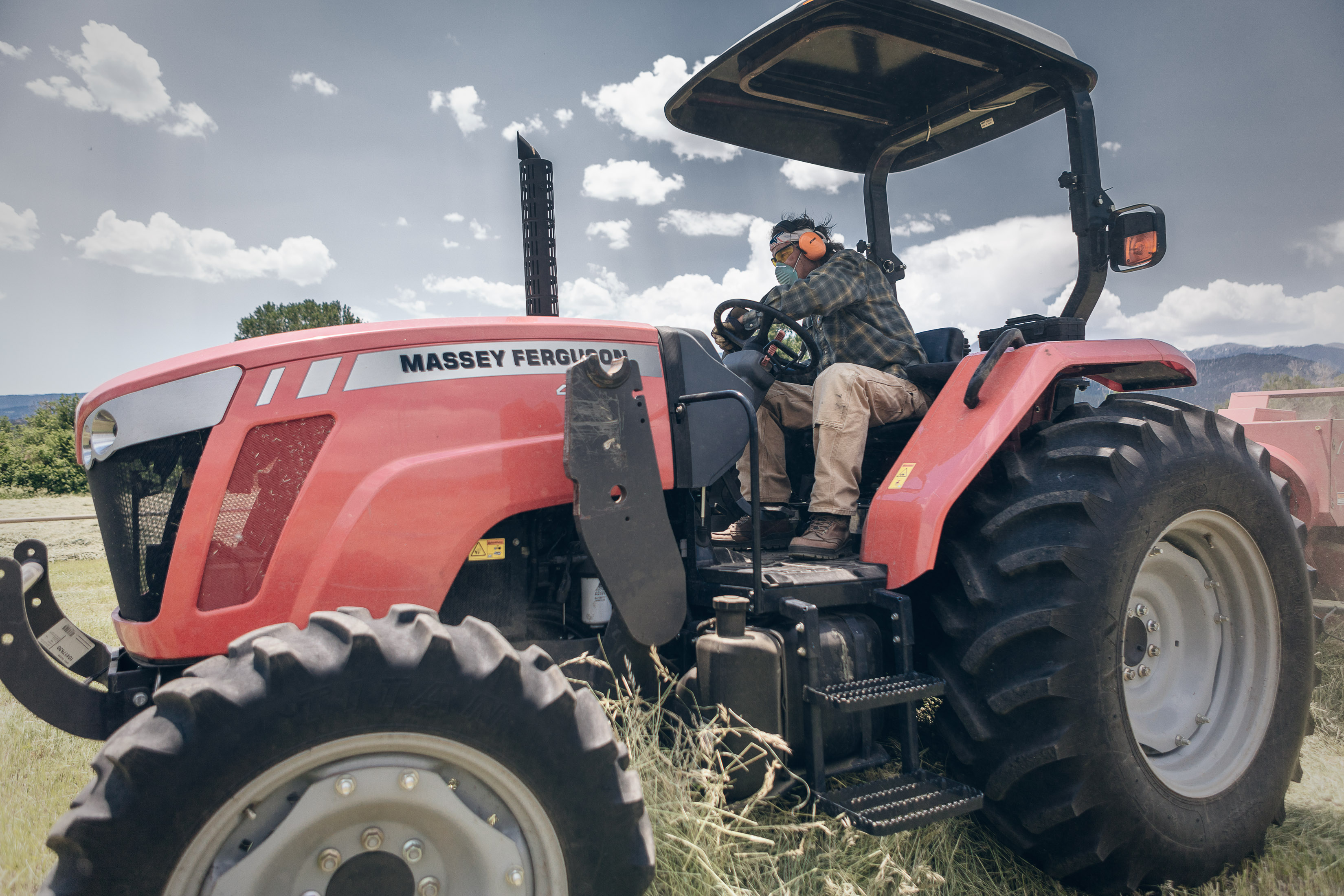 a man drives a tractor on a hay farm in Howard Colordo