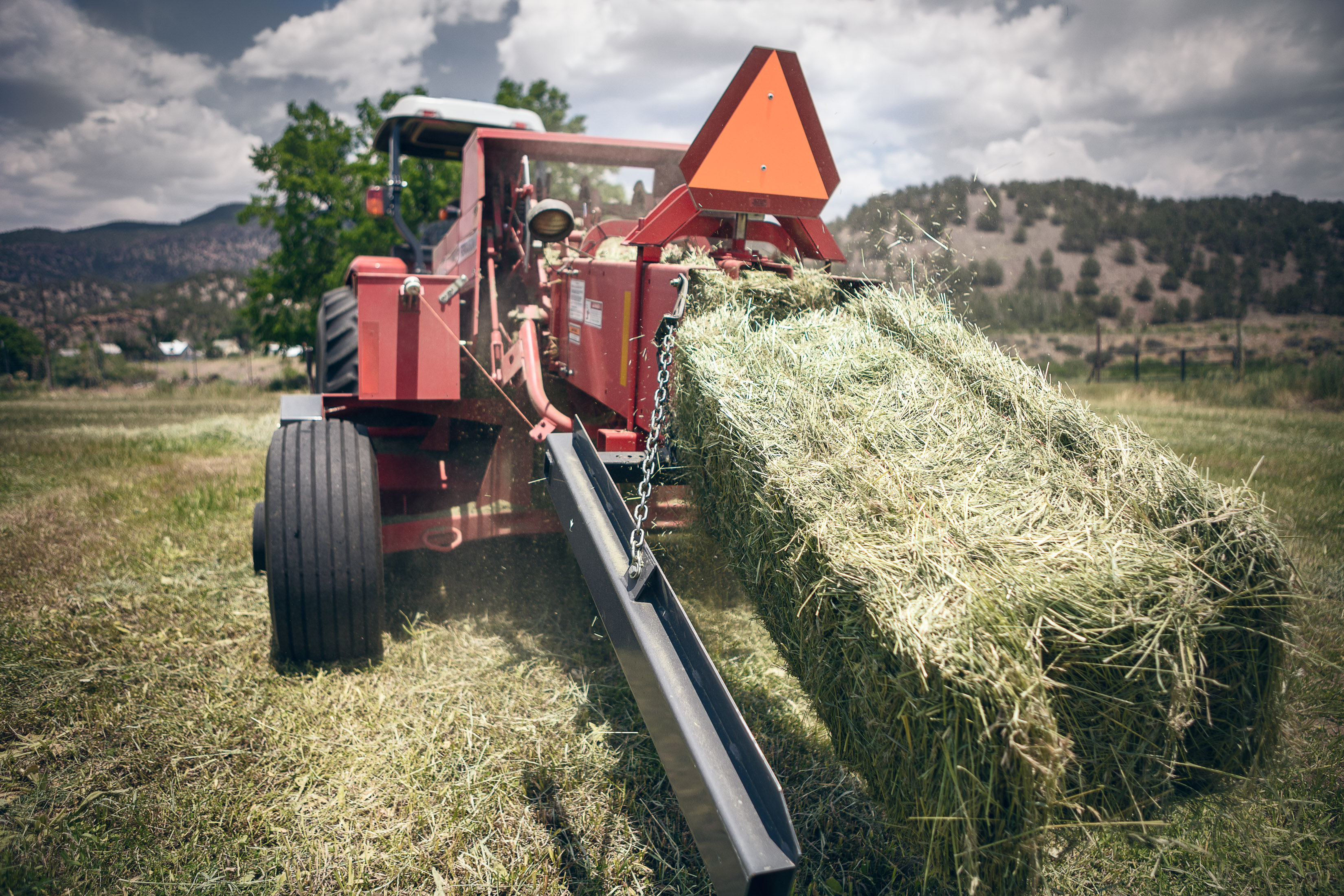 a bail of hay is dispensed from a tractor on a hay farm in Howard, Colorado