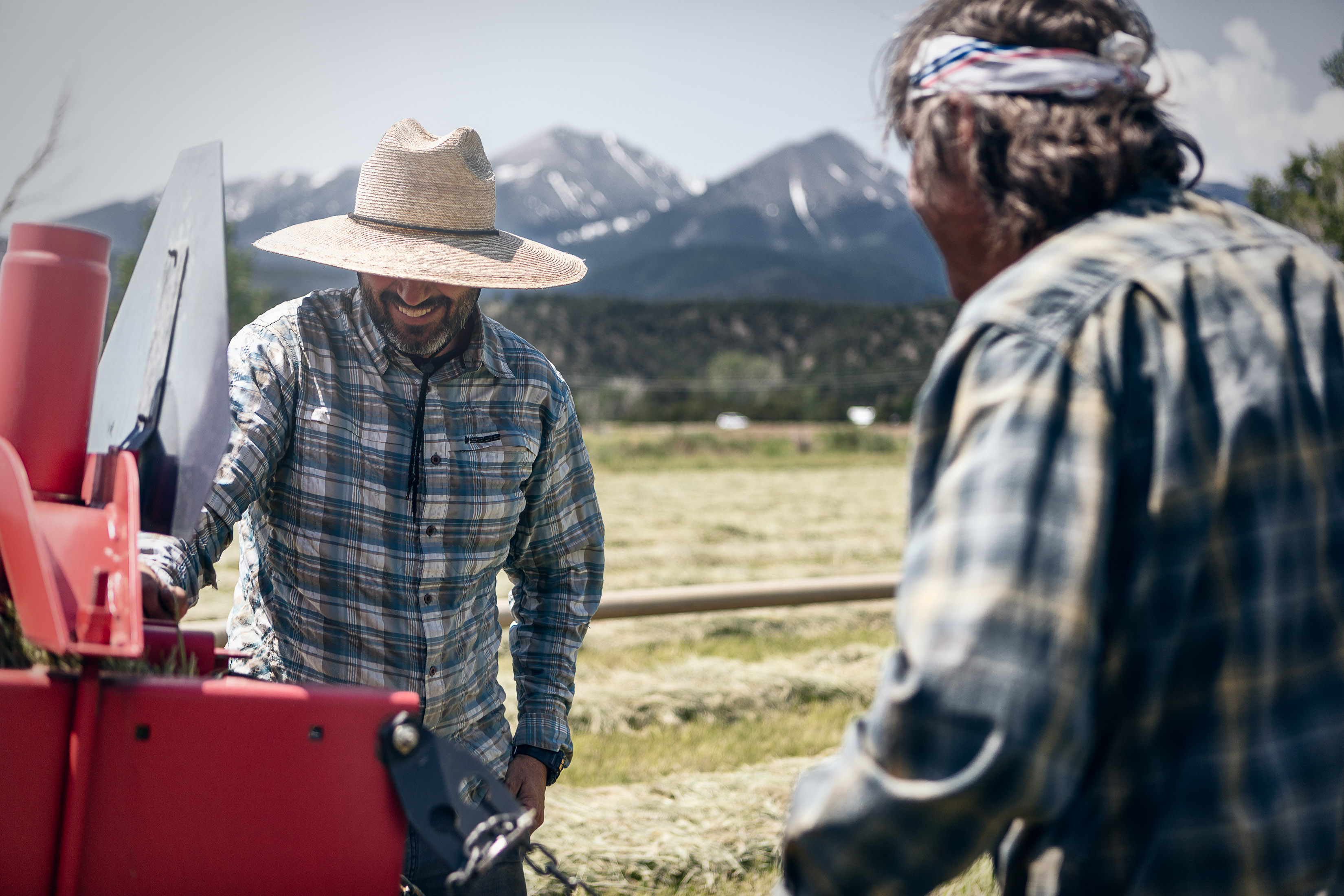Two men talk next to a tractor on a hay farm in Howard, Colorado