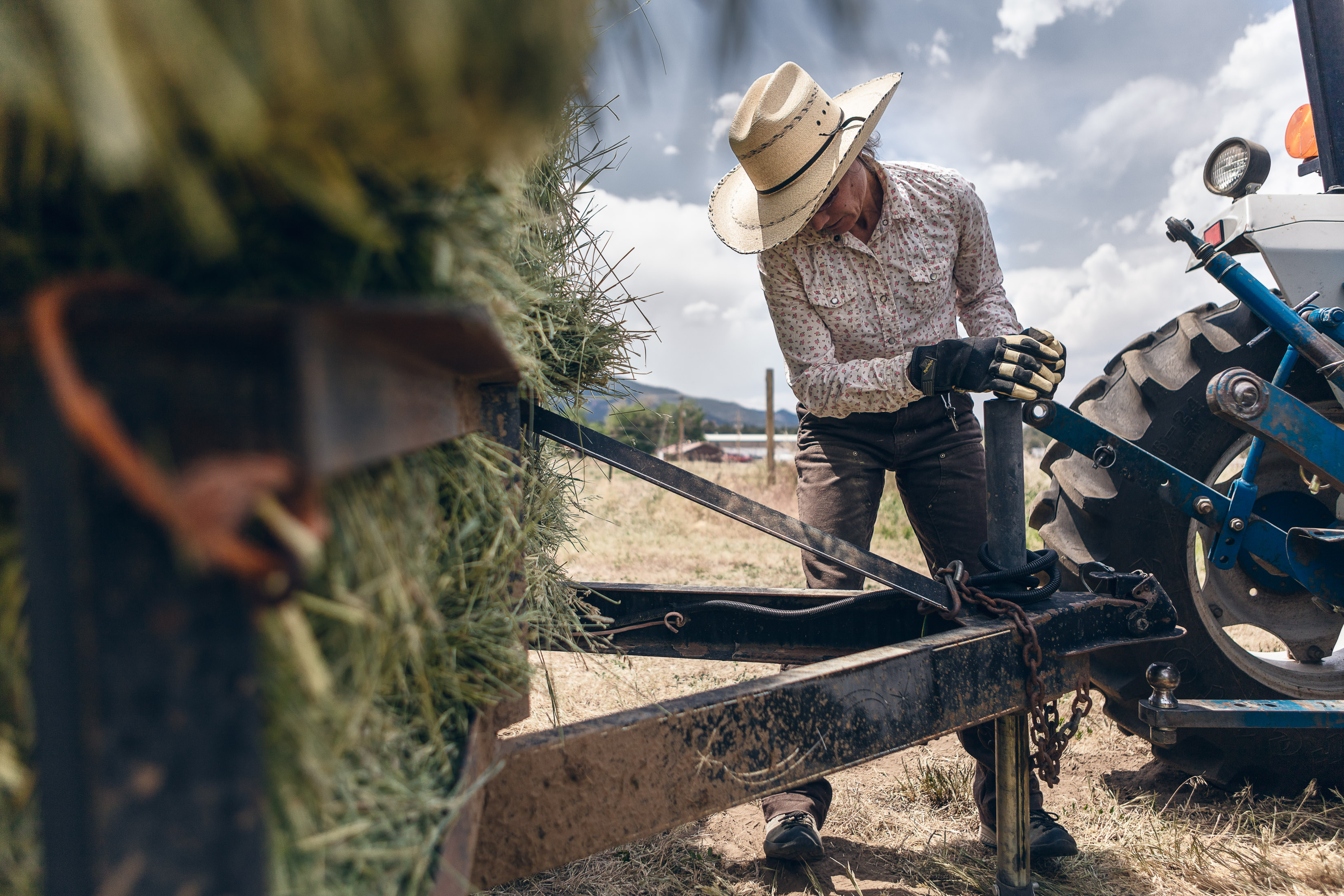 A woman hooks up a trailer for bailing hay on a hay farm in Howard, Colorado