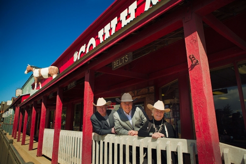 three people stand by railing outside a western wear store in Colorado