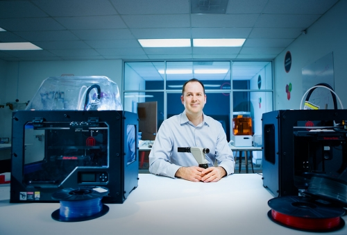 engineering researcher with 3d printers in foreground