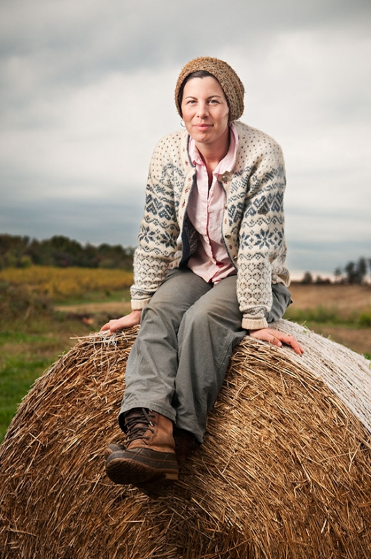An organic farmer sits on a bail of hay at her farm