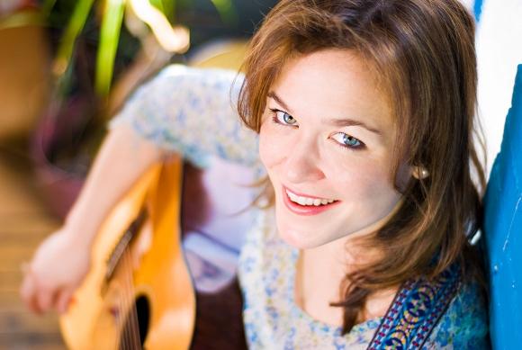 Folk singer Julie Foldesi strums a guitar on a staircase